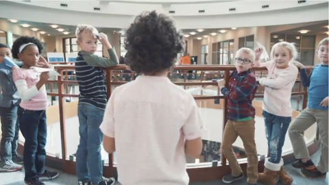 children gathered in a library for a paper airplane flight test