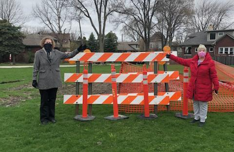 Two women standing in front of orange and white construction barrier