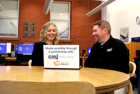 Attached Picture: Sycamore Public Library Director, Monica Dombrowski (left)and Chad Jewett, Owner of CMJ Technologies(right).