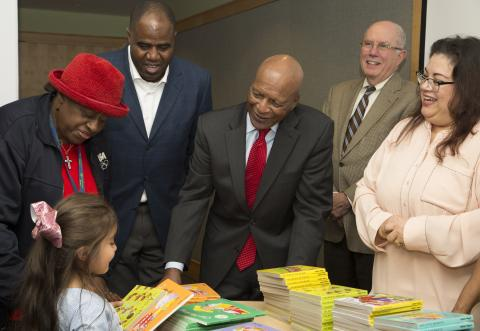 Illinois Secretary of State and other elected officials give a book to a young girl at Waukegan Library's Family Reading Night. Photograph shows, L-R: Isabella (age 4); Lake County Commissioner Mary Ross Cunningham; Mayor Sam Cunningham, Secretary White, Judge Charles W. Smith, Executive Director Selina Gomez-Beloz