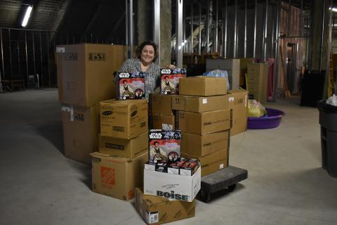 Community Engagement Officer, Denise Zielinski, stands with boxes of donations from the Giving Tree Drive.