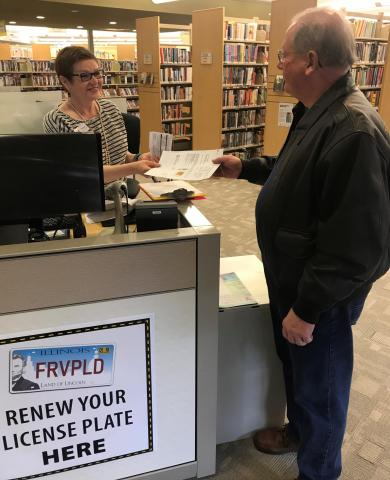 A Fox River Valley staff member hands a completed sticker sheet to a patron.