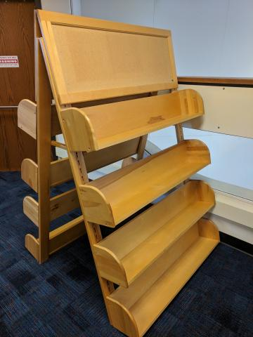 Eight adjustable wood shelves on an A-Frame unit, with a cork board on top
