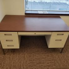 Office desk with wood-look top and drawers.